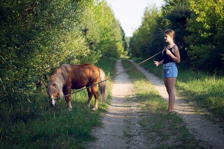 Teenage girl walking with a pony colt on a leash along a country road
