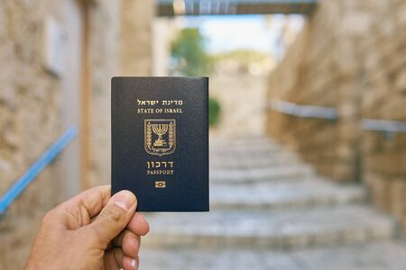 Male hand holding the passport of the State of Israel on the old narrow street background