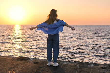 Teenage girl standing with hands raising up on a sea pier at sunset. Back view.