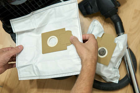 New dust bag in male hands above of a vacuum cleaner during the dust bags replacement