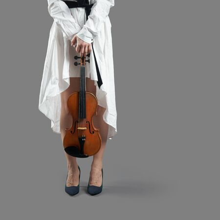 Young woman musician wearing a white dress holding a violin in her lowered hands at her feet isolated on the gray background with shadows Stock Photo