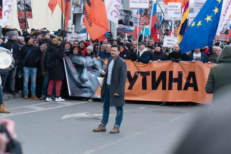 Moscow, Russia - February 29, 2020. Russian opposition leaders carry a banner at the head of the March of Boris Nemtsov. Oppositionist Ilya Yashin on the foreground. Writing: Putin to resign