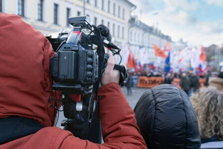 Videographer is reporting from a city street during a mass political action in Moscow, Russia. He holds the camera on his shoulder