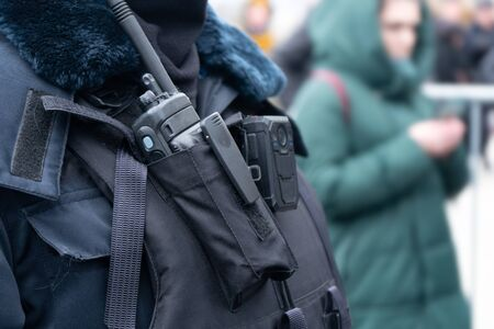 Police radio device on the chest of a russian policeman close up on the street. Police communication tool