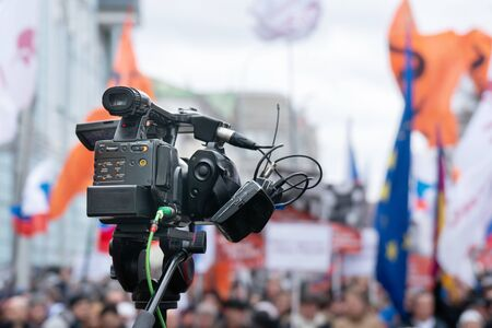 Videographer is reporting from a city street during a mass political action in Moscow, Russia. Camera is up of the crowd