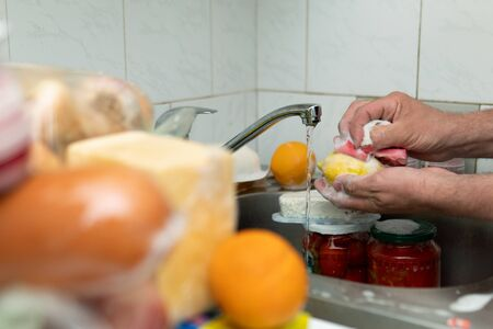 Male hands washing foodstuff just purchased in a shop with a sponge in soap suds in a kitchen sink in coronavirus pandemia period