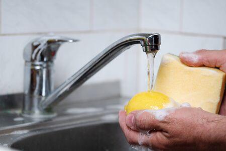 Male hands washing a lemon with a sponge in soap suds in a kitchen sink