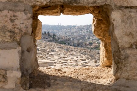View of jewish cemetery on Mount of Olives in Jerusalem through a hole in the wall