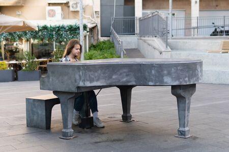 Teenage Girl plays music on the piano outdoors on Haifa street, Israel in the evening