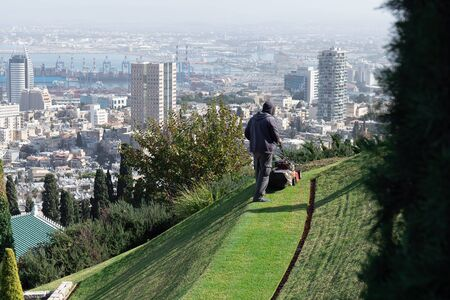 Man mowing a lawn using a lawnmower in Bahai Gardens on the Haifa panorama background