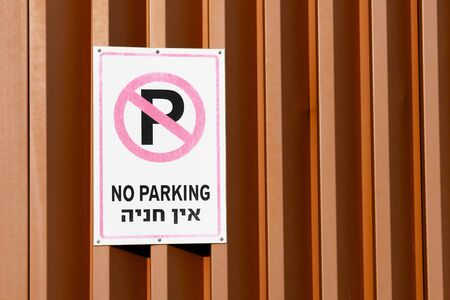 No Parking street sign with writings on english and hebrew on a metallic wall in Israel