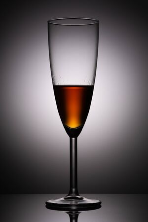 A glass of cognac on the background of a light spot in the dark with a reflection in the glossy surface of the table. Product photography studio shot. Фото со стока