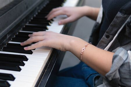 Close up of the hands of a teenage girl playing piano on the city street Фото со стока