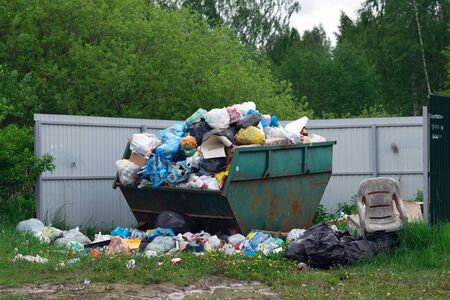 Overflowing dumpster at russian countryside in summer day Фото со стока