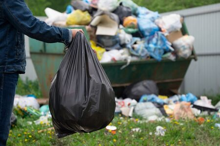 Man in denim suit throws a plastic bag with a garbage to junk container outdoors at countryside. Garbage disposal concept. Фото со стока