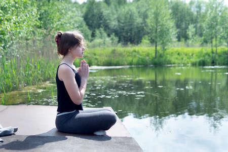 Teenage caucasian girl doing yoga exercise on the pond pier