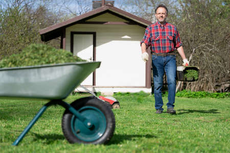 Happy man in a checked shirt carry a full of grass lawnmower container to emptying it into a wheelbarrow