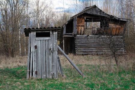 Old wooden village lavatory near an abandoned broken house at countryside in springtime