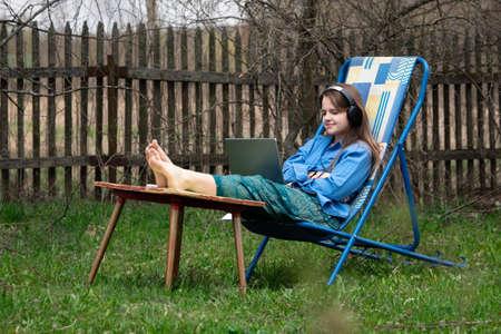 Teen girl takes part in a school online webinar sitting outdoors in springtime