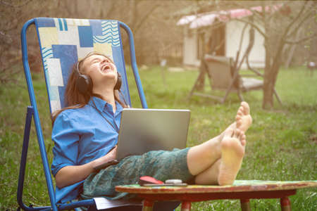Teen girl laughing during online conference with her school friends sitting in a deckchair outdoors in springtime