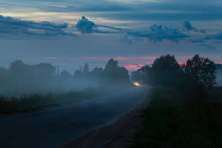 Russian countryside road with distant headlights of a car at summer foggy night