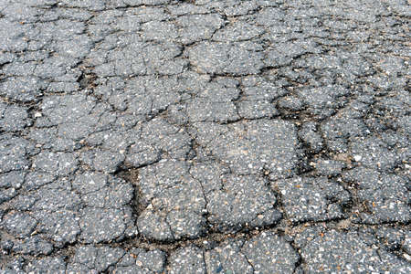 Fragment of a russian countryside road with a cracked asphalt. Old broken asphalt texture