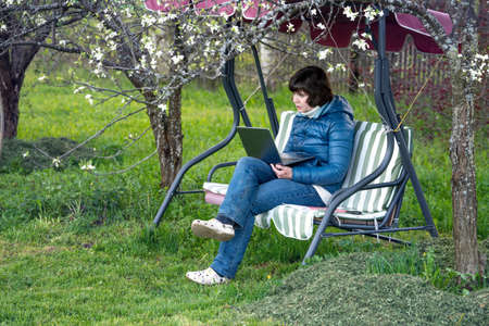 Real female teacher conducts a lesson on the Internet while sitting in the garden on an outdoor garden swing during coronavirus quarantine. Side view Фото со стока