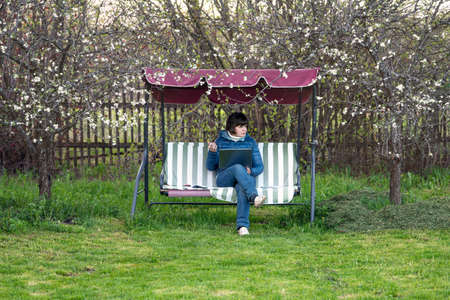 Real female teacher conducts a lesson on the Internet while sitting in the garden on an outdoor garden swing during coronavirus quarantine