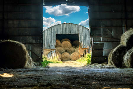 View of the hay bales being stored in an old wooden barn from the another hay barn