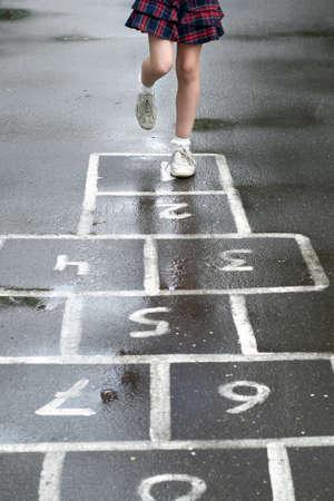 Legs of a schoolgirl who plays hopscotch on the asphalt outdoors