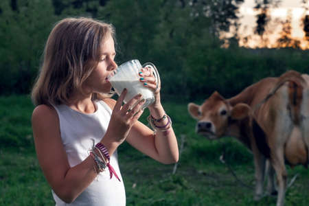 Teenage girl drinks fresh milk on the pasture with a cow on the background in evening Stock Photo