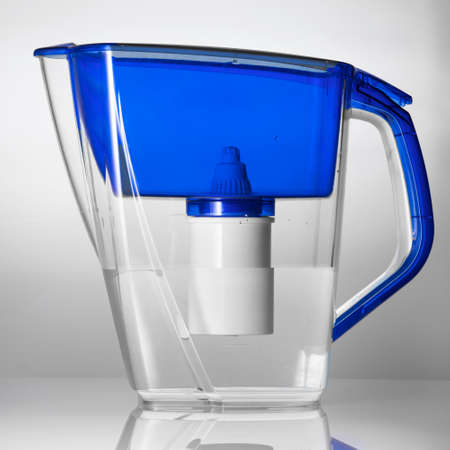 Studio shot of a plastic water filter jug standing on the reflecting surface