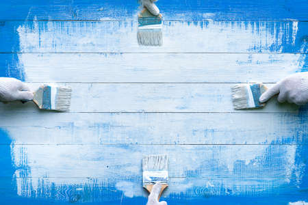Creative background with four hands painting blue wooden boards with white paint