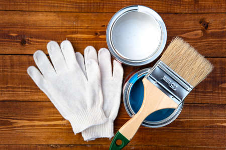 Tools needed for a painting work: paint brush, paint bucket, protective gloves lying on wooden boards