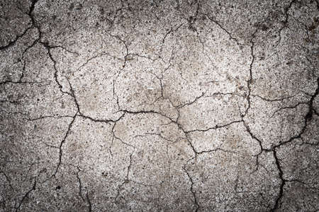 Texture with cracks of old paint on the pavement. Cracked surface of a road marking background. Abstract background with a surface covered with cracks.