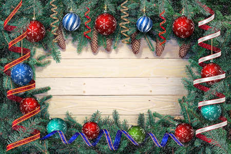Christmas or New Year background with fir branches on the wooden boards decorated with balls and ribbons with snow Stock Photo