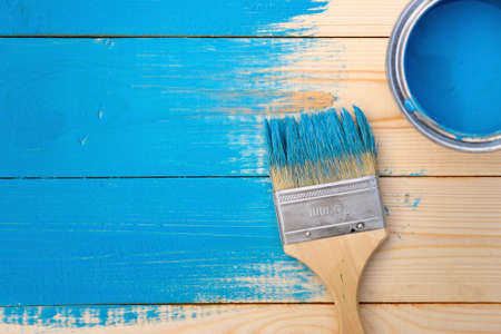 Paint brush lying on the wooden boards painted in blue and white paint