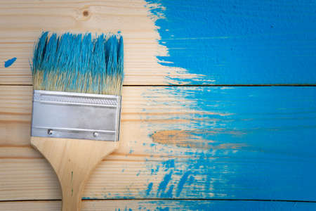 Painting works background with paintbrush in blue paint on the wooden not completely painted boards