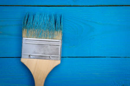 Background with paintbrush in blue paint on the wooden completely painted blue boards