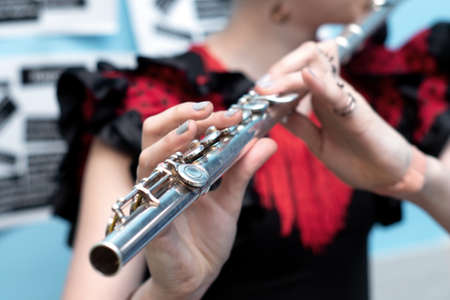 Girl plays the flute close up in school