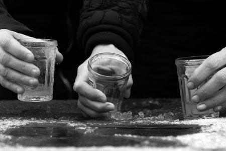 Hands of three women drinking vodka outdoors in winter