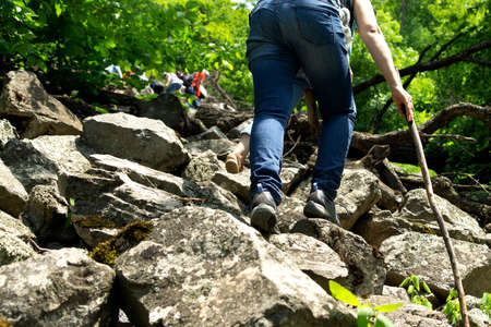 Tourists climb over the stones in the Armenian mountains Stock Photo