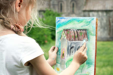 Little blonde schoolgirl draws an ancient castle from nature