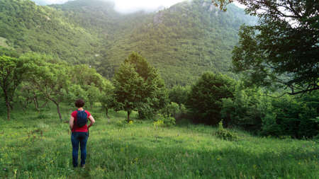 Woman with backpack stands in armenian mountains in early morning