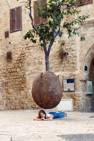TEL AVIV, ISRAEL - December 2, 2019: Smiling Teenage girl lies under the Floating Orange Tree by Israeli sculptor Ran Morin.