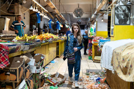 Haifa, Israel - November 24, 2019. Teenage girl on the agricultural market in evening just before closing
