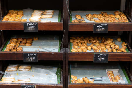 Counters of a small bakery shop filled with tasty freshly prepared buns in Haifa, israel Фото со стока