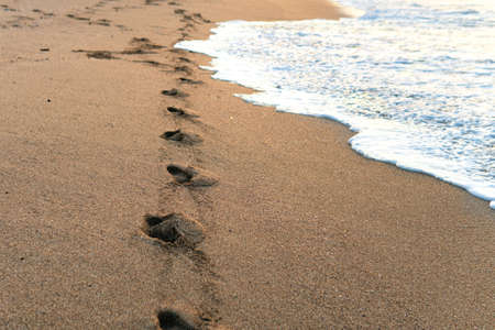 Footprints of bare feet on the sand of a seaside near the water at sunset Фото со стока