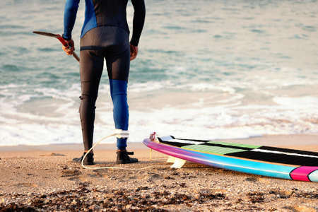 Male surfer wearing a wetsuit standing on the sea beach sand ready to surf in november in Israel