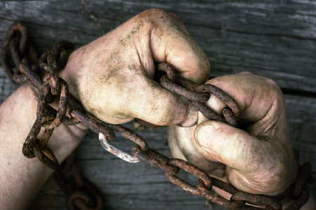 Male hands trying to free themselves from the chains on the wooden boards close up